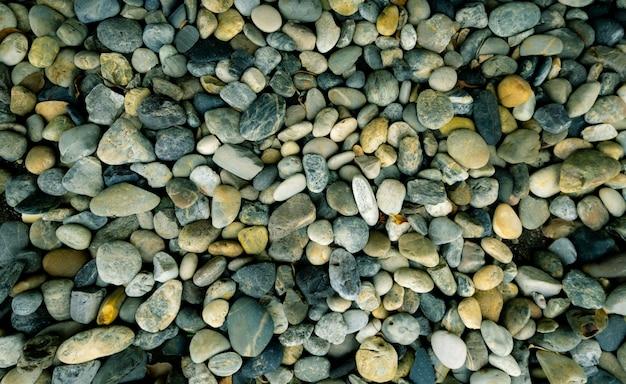 Fundo de textura de pedra pequena. pedra de seixo na praia.