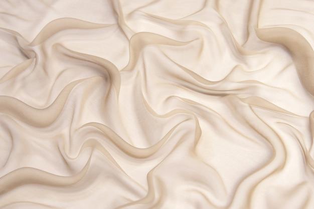 Fundo de textura de tecido de chiffon de seda de cor champanhe abstrata.