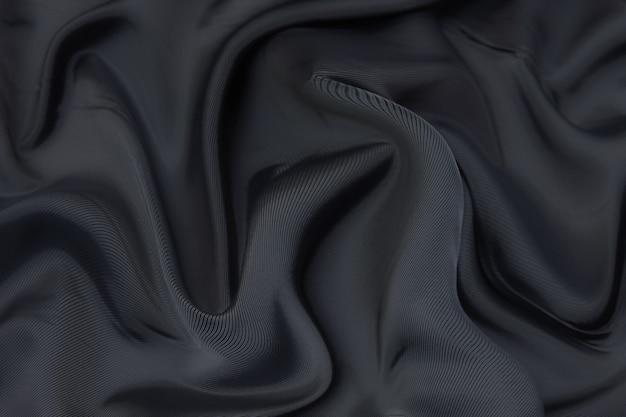 Fundo de textura de tecido preto, tecido ondulado de cor preta escorregadia, cetim luxuoso ou textura de tecido de seda ou lã.
