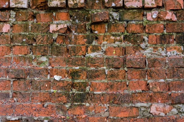 Fundo de tijolo vermelho. parede de rua velha, arruinada.