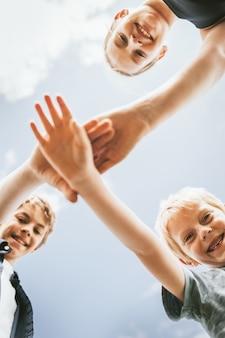 Fundo de trabalho em equipe, crianças empilhando as mãos no meio, foto de família