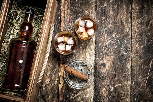 Fundo de uísque. uma garrafa de uísque em uma velha caixa com copos e um charuto. sobre um fundo de madeira.