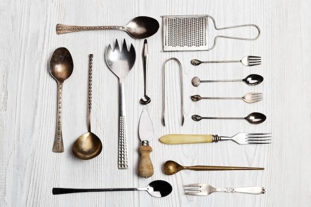 Fundo de utensílios de cozinha - colheres, garfos, faca de queijo, ralador, tenaz
