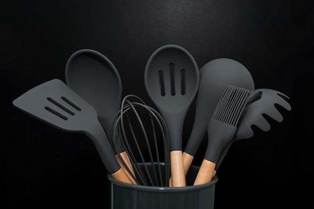 Fundo de utensílios de cozinha com copyspace, conceito de decoração de cozinha em casa, utensílios de cozinha preto, acessórios de borracha no recipiente. restaurante, culinária, culinária, tema de cozinha. espátulas e escovas de silicone