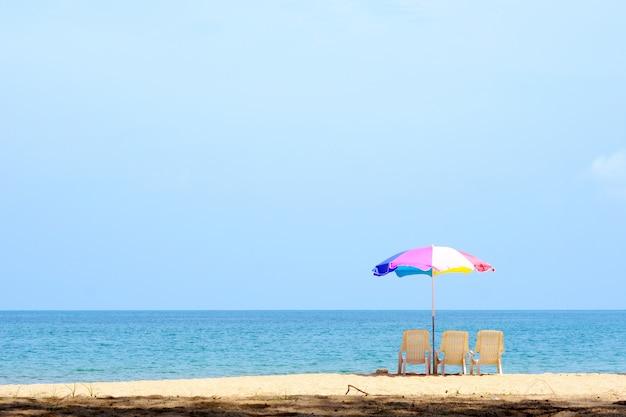 Fundo de verão, cadeira e guarda-chuva colorida no fundo da praia e do mar