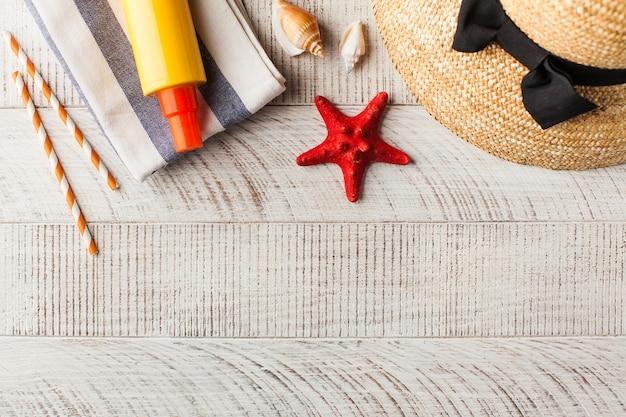 Fundo de verão chapéu conchas protetor solar em mesa de madeira com espaço de cópia