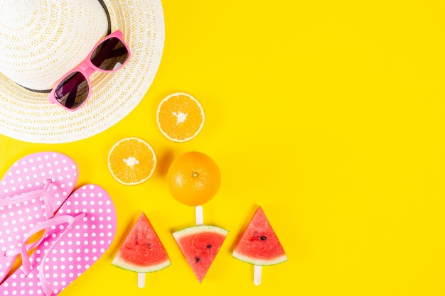 Fundo de verão. chapéu, óculos de sol, chinelo, melancia e laranjas em fundo amarelo.