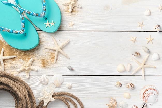 Fundo de verão com conchas, corda, estrela do mar e flip-flops em fundo de madeira clara
