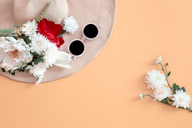Fundo de verão com flores e um chapéu.