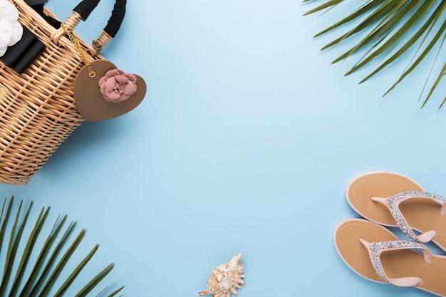 Fundo de verão com folhas de palmeira, chinelos, bolsa de praia de palha sobre um fundo azul pastel claro, conceito de viagens e férias, vista superior