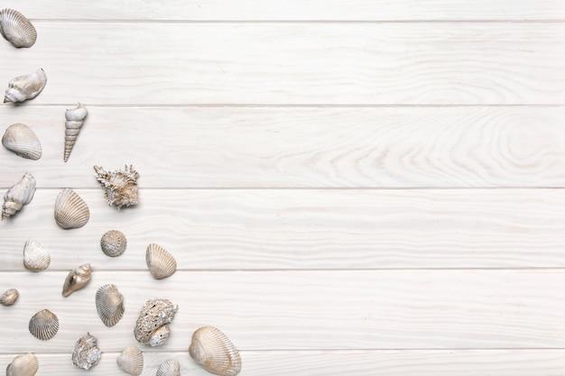 Fundo de verão com mesa de madeira branca com muitas conchas.