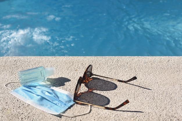 Fundo de verão com piscina, óculos de sol, máscara e gel hidroalcoólico.