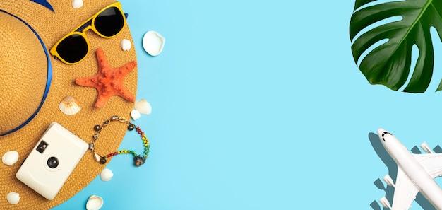 Fundo de verão de viagens. óculos de sol, chapéu, folhas tropicais de palmeira, conchas, acessórios de avião e praia em um fundo de cor azul. férias turísticas, relaxamento e conceito de verão. p de alta qualidade