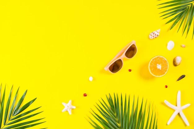Fundo de verão. folhas de palmeira com estrela do mar e óculos de sol em fundo amarelo. viagem. copie o espaço