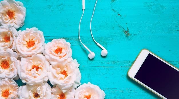 Fundo de verão linda com rosas frescas, smartphone e fones de ouvido brancos em uma velha mesa de madeira pintada