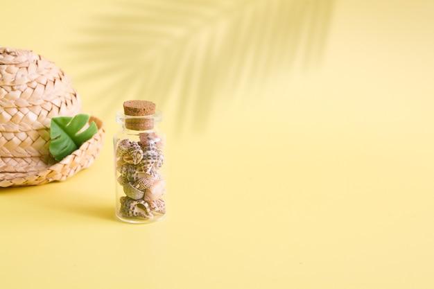 Fundo de verão minimalista com mini garrafa e pequenas conchas, chapéu com sombra de folhas de palmeira na superfície amarela