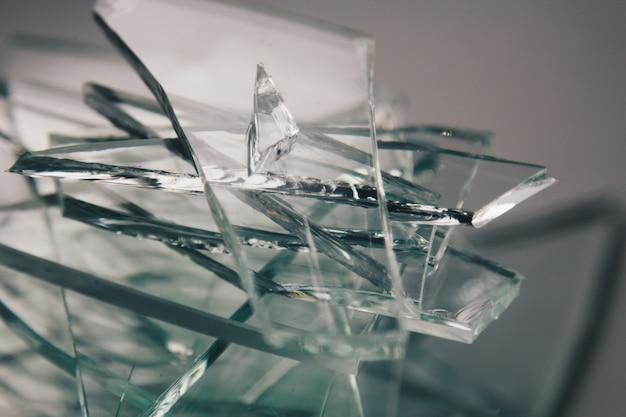 Fundo de vidro quebrado para suas imagens isoladas em branco. muitos fragmentos de vidro grandes espalhados por um martelo como conceito de violência.