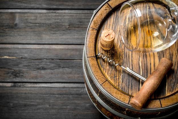Fundo de vinho. um velho barril de vinho branco. sobre um fundo de madeira.