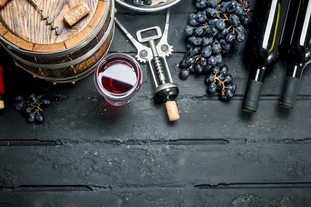 Fundo de vinho. vinho tinto com uvas e barrica velha. sobre um fundo preto rústico.