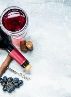 Fundo de vinho. vinho tinto com uvas e saca-rolhas. sobre um fundo rústico.