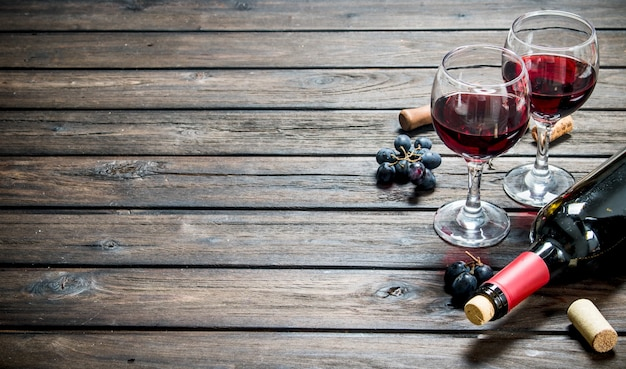 Fundo de vinho. vinho tinto com uvas pretas. sobre um fundo de madeira.