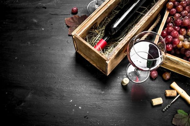 Fundo de vinho. vinho tinto em uma velha caixa com um saca-rolhas.