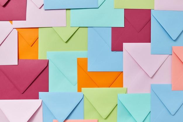 Fundo decorativo colorido de envelopes em branco feitos à mão como um padrão.
