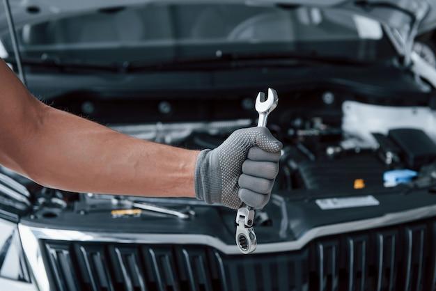 Fundo desfocado. a mão na luva segura a chave inglesa na frente de um automóvel quebrado