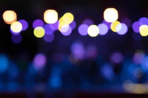 Fundo desfocado bonito de performances noturnas com luzes amarelas, roxas e azuis.