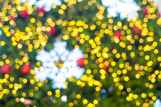 Fundo desfocado, close-up floco de neve na árvore de natal com luz de bokeh