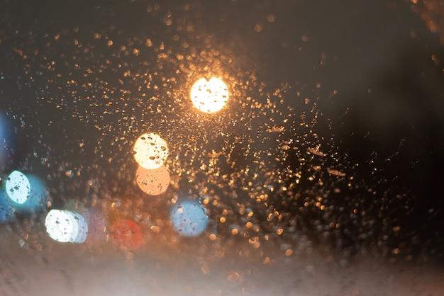 Fundo desfocado com gotas de chuva e luzes