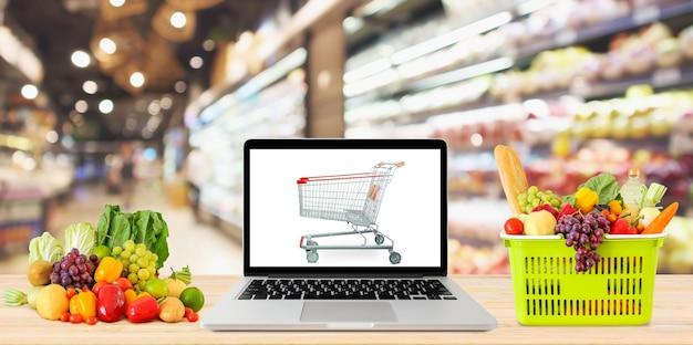 Fundo desfocado corredor do supermercado com computador laptop e carrinho de compras