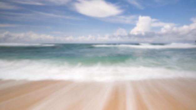 Fundo desfocado da paisagem marítima na praia com movimento dramático da água e nuvens pela manhã