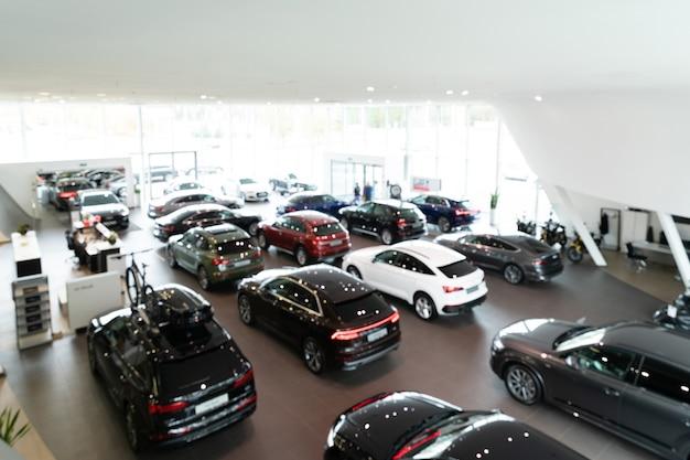 Fundo desfocado de carros novos exibidos em panorama de showroom de luxo