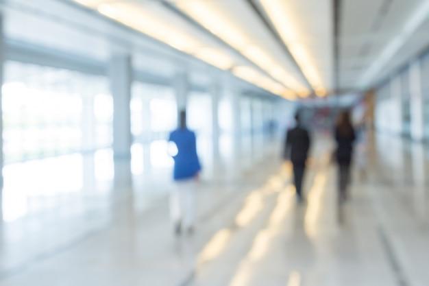 Fundo desfocado de empresários andando no corredor de um centro de negócios