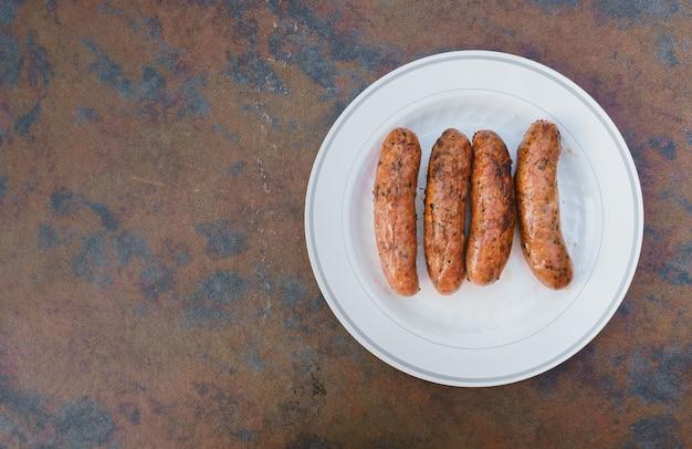 Fundo desfocado de festa no jardim e salsicha marrom e salsichas de porco de mesa de cozinha em chamas