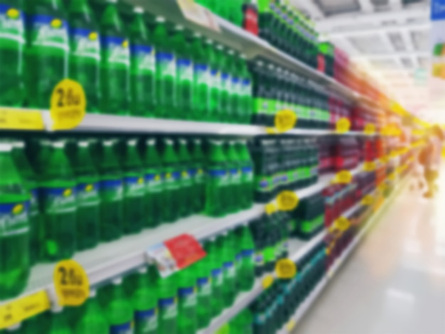 Fundo desfocado de garrafas de refrigerantes nas prateleiras na loja de varejo