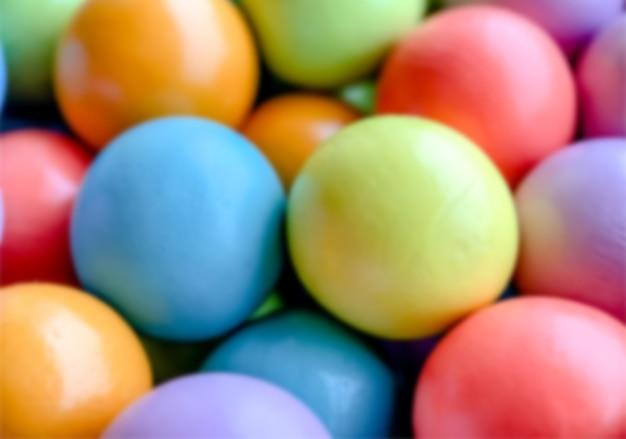 Fundo desfocado de pequenas bolas de madeira brilhantes multicoloridas de azul amarelo vermelho lilás e verde