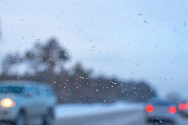 Fundo desfocado do para-brisa de um carro com flocos de neve e carros ao fundo