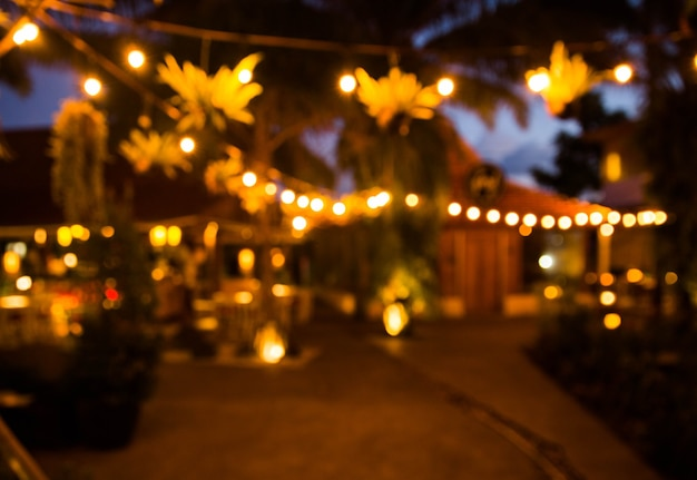 Fundo desfocado: o restaurante com mesas e cadeiras desfoca o fundo com a luz do bokeh. hora da noite