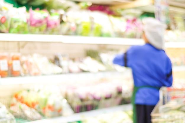 Fundo desfocado, pessoal de supermercado borrão em prateleiras de produtos, conceito de plano de negócios