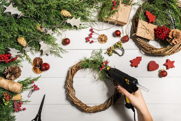 Fundo diy artesanal de natal. fazendo artesanato coroa de natal e ornamentos. lazer da mulher, ferramentas e bugigangas para a decoração do feriado. vista superior da mesa de madeira branca com mãos femininas.