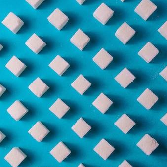 Fundo do alimento com açúcar no papel azul da cor.