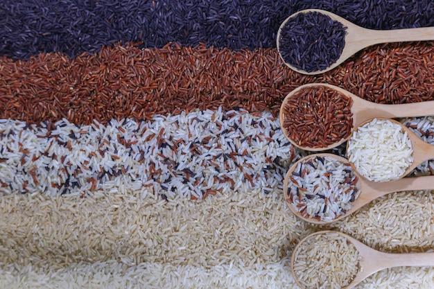 Fundo do alimento com ideia superior de cinco fileiras do arroz em uma colher de madeira.