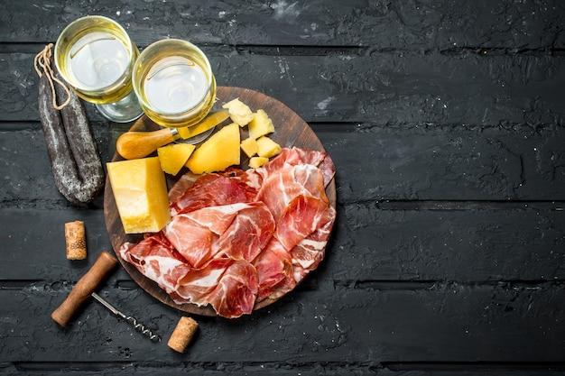 Fundo do antipasto. aperitivos italianos com vinho branco. sobre fundo preto rústico.