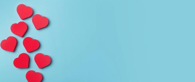 Fundo do banner do dia dos namorados. corações vermelhos sobre um fundo azul mínimo. conceito de amor, romance e corações.