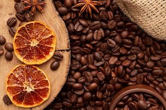 Fundo do café com a decoração de laranjas secadas, anis de estrela. Xícara de café e feijão
