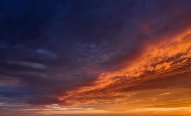 Fundo do céu do sol vibrante com nuvens escuras iluminadas pela luz solar laranja.