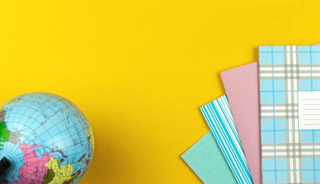 Fundo do conceito de educação com o globo e o diário escolar ou cadernos coloridos na mesa amarela da área de trabalho, copie o espaço e a foto da vista superior