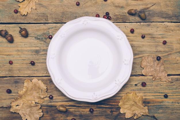 Fundo do conceito de jantar de ação de graças: prato branco, colher e garfo sobre uma mesa rústica de madeira com folhas de outono, bagas vermelhas e bolotas